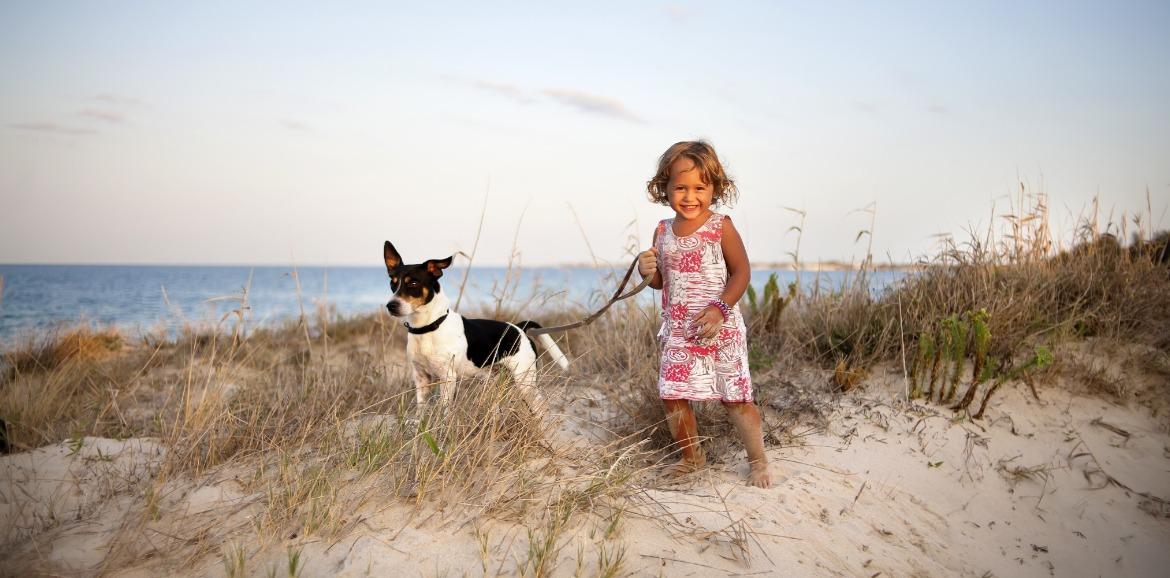 little girl with dog on the beach | Sunset Vacations