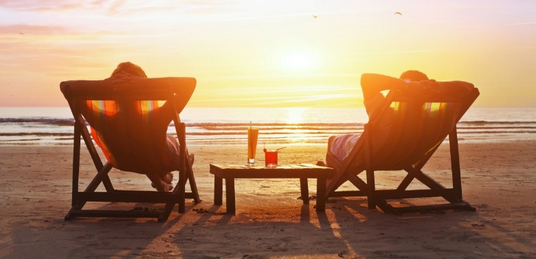 two people sitting in beach chairs watching the sunset | Sunset Vacations