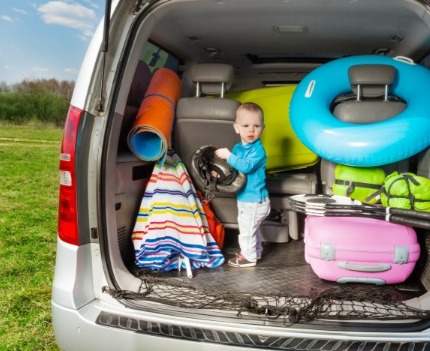 Kid in minivan packed for the beach | Sunset Vacations
