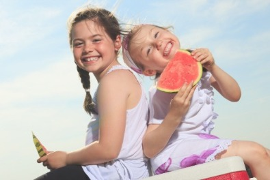Kids having watermelon on the beach | Sunset Vacations