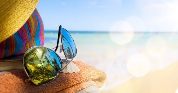 sunglasses and beach accessories sitting on the beach | Sunset Vacations