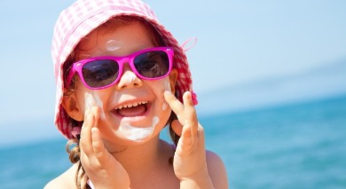 little girl wearing sunglasses, hat, and sunscreen on the beach | Sunset Vacations