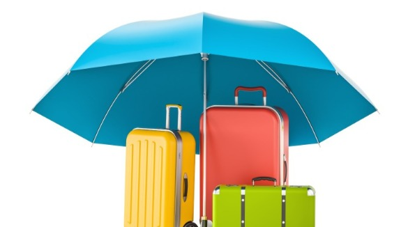 umbrella protecting luggage | Sunset Vacations