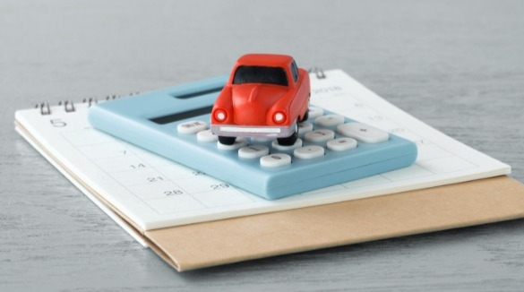 car, calculator, calendar on a table | Sunset Vacations